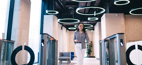 Businesswoman walking through entrance in office building Canvas Print