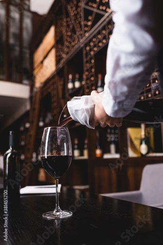 Selective focus of sommelier in shirt pouring wine from decanter in glass