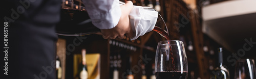 Foto Panoramic shot of sommelier holding towel while pouring wine from decanter in re