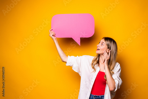 Fototapeta Portrait of a happy young woman holding empty speech bubble standing over yellow background obraz