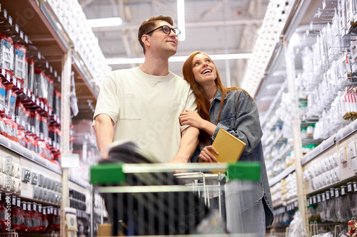 Photo caucasian couple shopping together, use information book and discuss, going to e