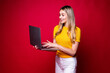 Portrait of smiling young woman holding, working on laptop pc computer isolated on red background.