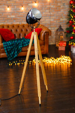 Vintage Wooden Lamp Projector Near The Classic Brick Wall Amd Christmas Lights On Background. Room In Loft Style With Dark Wooden Floor