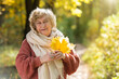 Gray-haired, smiling elderly woman in an autumn park. Happy old age, walking in nature, positive emotions.