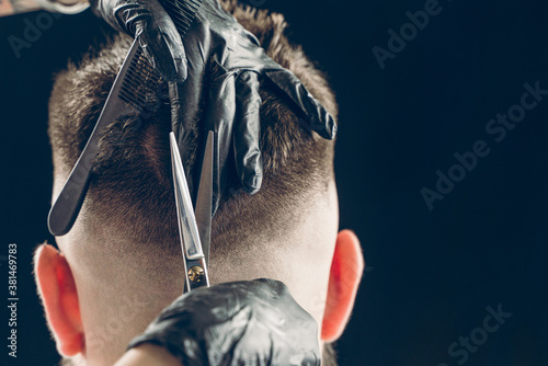 Cropped shot of barber cutting hair of customer with scissors Fototapeta