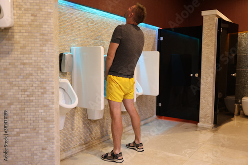 Fototapeta Man stands with his back near toilet and looks up