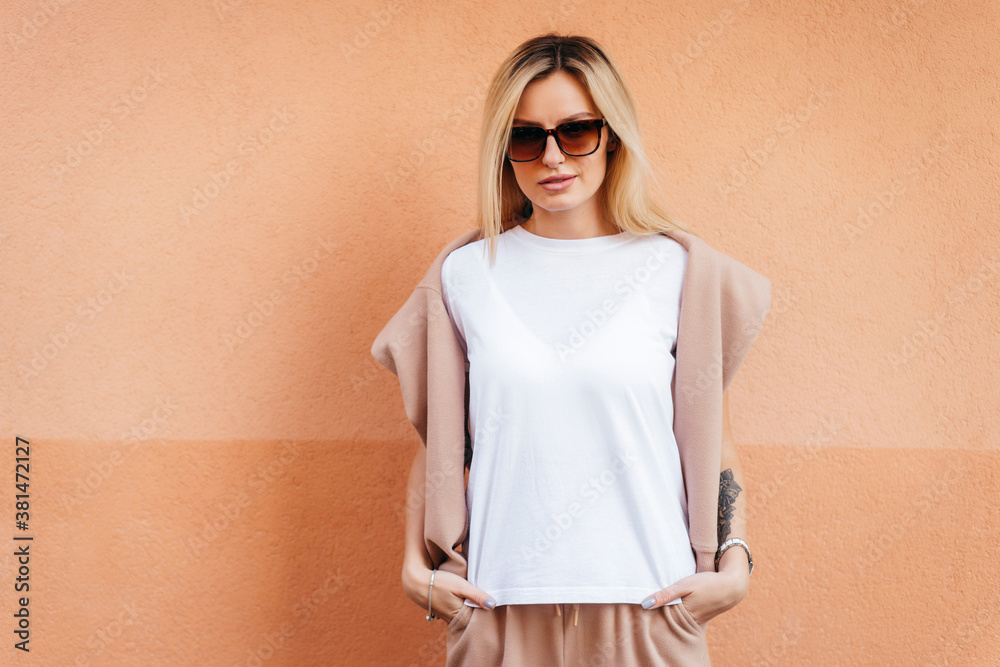 Fototapeta Stylish blonde girl wearing white t-shirt and glasses posing against street