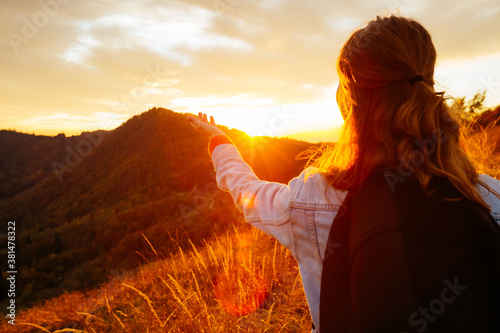 Fototapeta Carefree hipster girl enjoying nature on top of mountain with sunset. obraz na płótnie