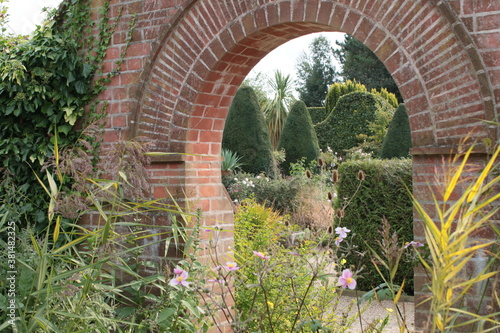 Leinwand Poster Landscape of English country garden with old brick stone red wall arch way path