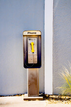 Old Fashioned Telephone Booth With Yellow Phone.