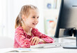 Smiling little girl at computer desk