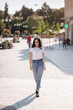 Attractive young woman in white shirt and jeans walking in the city