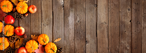 Obraz Autumn corner border with pumpkins, leaves and apples. Top down view on a rustic dark wood background with copy space. - fototapety do salonu