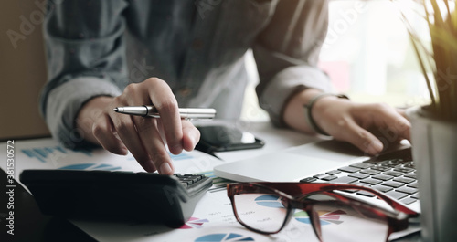 Valokuva Close up of businessman or accountant hand holding pen working on calculator to