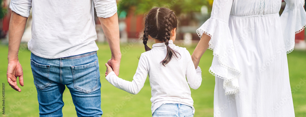 Fototapeta Portrait of enjoy happy love asian family father and mother holding little asian girl hand in moments good time in summer park at home