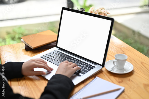 Vászonkép Croppped shot of bussinesswoman using laptop with white screen on wooden table