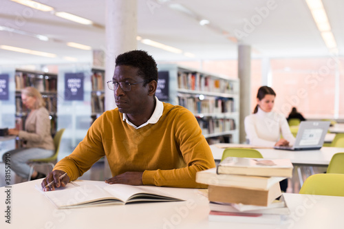 Vászonkép Intelligent african-american male student engaged in research working with books in university library