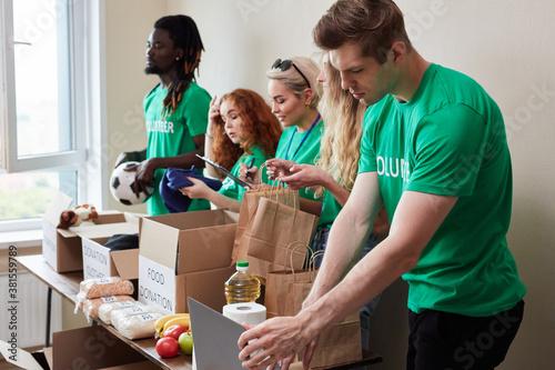 kind diverse volunteers work as team, have carboard boxes with donation clothes Tapéta, Fotótapéta