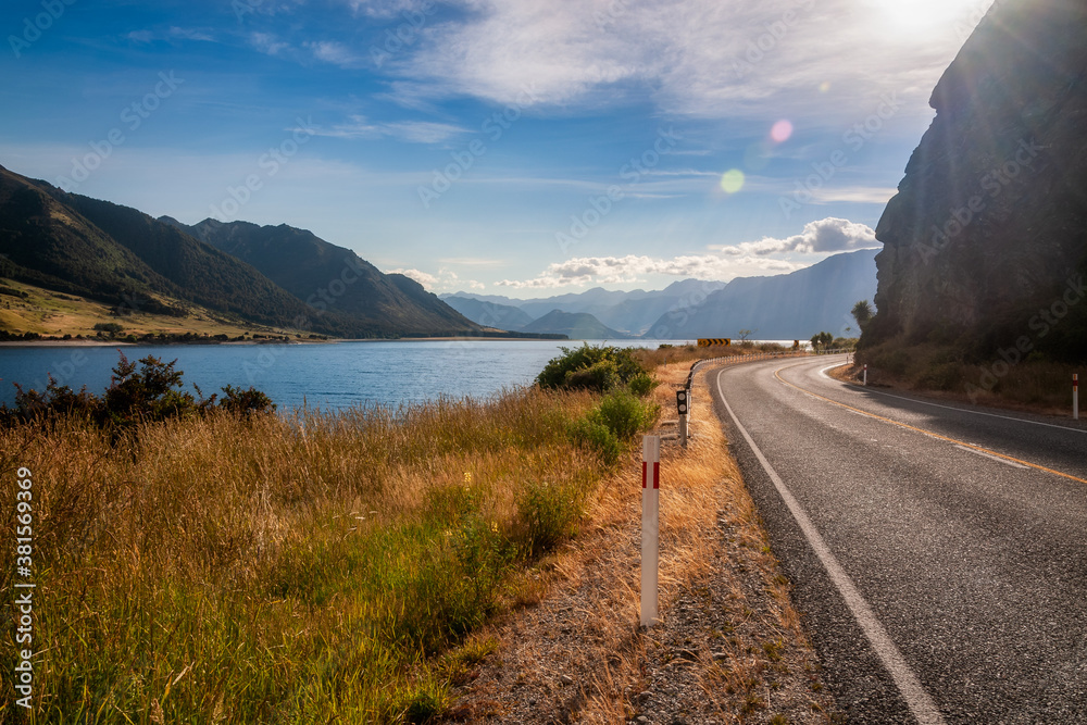 Fototapeta Sun flare in the morning at Makarora Country Road (Highway 6), a scenic alpine road at the Neck in between the lakes Wanaka and Hawea in Mount Aspiring National Park, Otago Region, New Zealand.