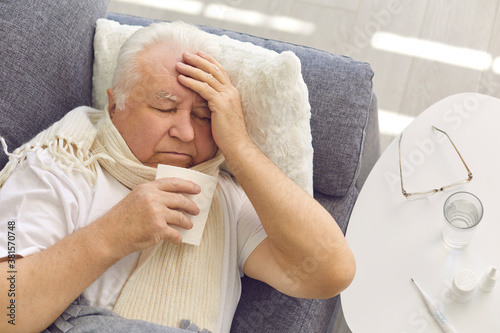 Senior man suffering from cold, flu or covid fever, coughing and having runny no Canvas Print