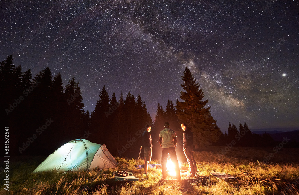 Fototapeta Night summer camping in forest. Bright campfire burning, three male tourists standing around fire near tent under beautiful dark starry sky and Milky way. Concept of tourism, camping in the mountains. - obraz na płótnie