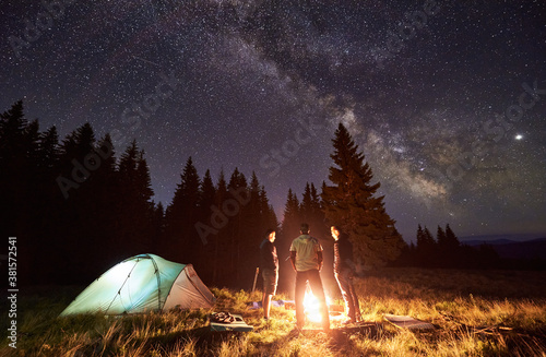 Fototapeta Night summer camping in forest. Bright campfire burning, three male tourists standing around fire near tent under beautiful dark starry sky and Milky way. Concept of tourism, camping in the mountains. obraz na płótnie
