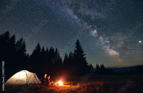 Photo Side view of loving couple sitting near bright burning campfire and tent, enjoying beautiful camping night together under dark sky full of shiny stars and bright Milky Way, warm summer night