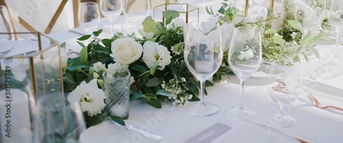 Photo Wedding banquet with clear glass goblets and wine glasses, white plates and gold