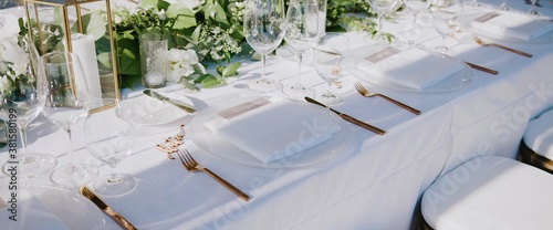Valokuva Wedding banquet with clear glass goblets and wine glasses, white plates and gold