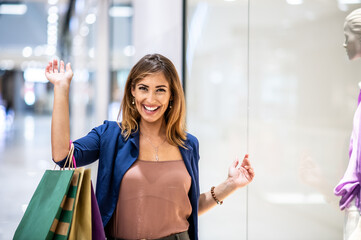 Young smiling cheerful attractive fashionable woman standing next to shopping window in mall, holding bags and looking at camera.