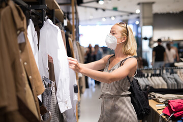 Fashionable woman wearing protective face mask shopping clothes in reopen retail shopping store. New normal lifestyle during corona virus pandemic.