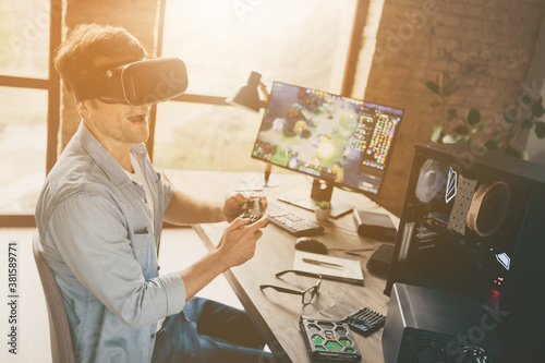 Fototapeta Profile side view of his he nice attractive cheerful cheery addicted guy geek freelancer playing online web network game walking vr at modern wooden industrial office work place station obraz