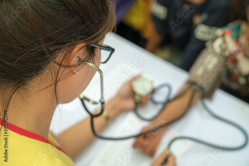 Obraz Volunteer nurse measuring blood pressure of poor Asian people outdoors closeup - fototapety do salonu