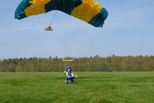 Tandem Skydiving. A Tandem Is Landing On The Green Field.