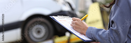 Fototapeta Insurance agent fills out paperwork after accident