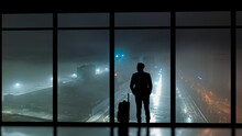 The Man With A Suitcase Standing Near A Panoramic Window Against The Night City