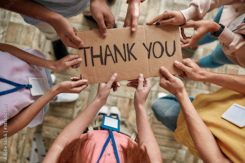 Fototapeta Top view of diverse young volunteers holding card with Thank you lettering while standing in charitable organization office