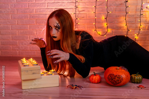 Fotografie, Obraz Halloween ginger Witch woman conjures with long scary nails and fashion halloween make up