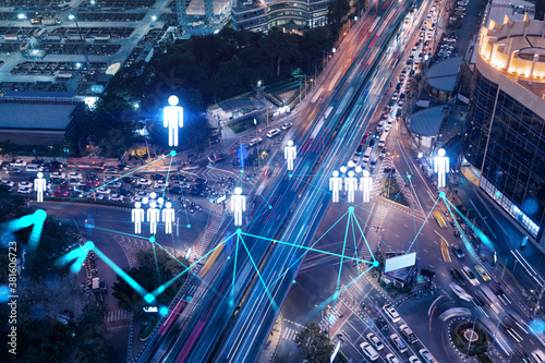 Fototapeta Social media icons hologram on top view of road, busy urban traffic highway at night. Junction network of transportation infrastructure. The concept of networking and success. Double exposure.