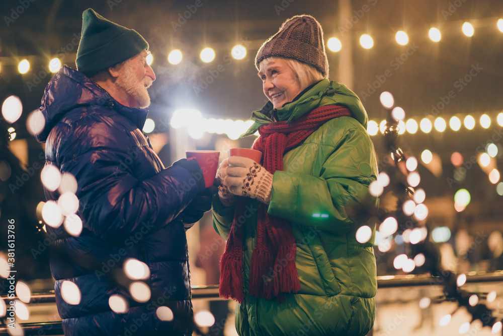 Obraz Photo of two people pensioner couple hold mugs drink eggnog comfortable cheerful smile newyear atmosphere wear mittens coat red scarf headwear x-mas night street park lights fair outside fototapeta, plakat