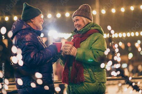 Fototapeta Photo of two people pensioner couple hold mugs drink eggnog comfortable cheerful smile newyear atmosphere wear mittens coat red scarf headwear x-mas night street park lights fair outside obraz