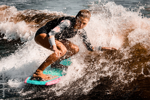 Fototapeta Active woman stands with bent knees on surf style wakeboard and ride on wave obraz