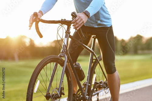 Cropped shot of professional road bicycle racer in sportswear cycling outdoors a Fotobehang