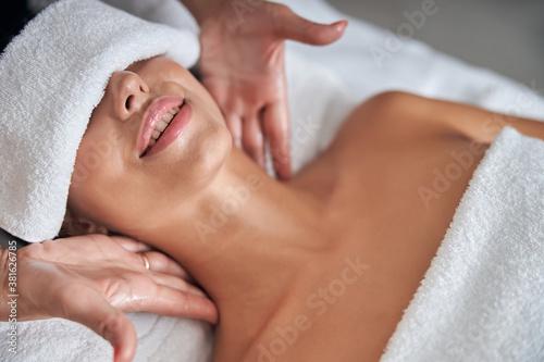 Fototapeta Masseur hands massaging young woman neck in spa salon obraz