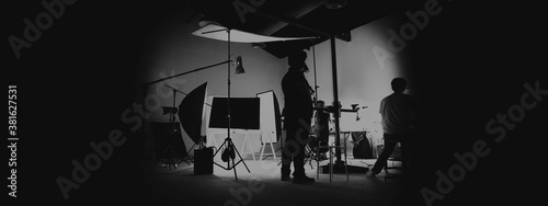 Obraz Behind the scene of photo shooting and production set up in the big studio. Professional crew team working and camera equipment in silhouette. such as light box, tripod, flashlight. and copy space. - fototapety do salonu