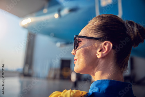 Fototapeta Happy smiling woman flight attendant in blue uniform enjoying good weather while