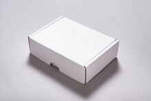 White Carton Cardboard Box For Postal Shipping On Grey Background