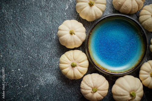 Obraz Cute white Baby boo mini pumpkins placed in circle with blue ceramic bowl in the middle - fototapety do salonu