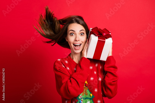 Fototapeta Close-up portrait of her she attractive glad cheerful amazed girl holding in hands festal gift celebratory having fun christmastime Eve Noel isolated bright vivid shine vibrant red color background obraz