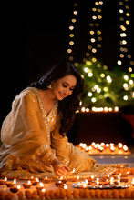 Woman Decorating Her House With Diyas On The Occasion Of Diwali
